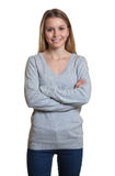 Standing woman in a grey sweater with crossed arms Stock Images