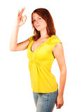 Standing woman with OK sign. Beautiful red-haired woman showing an OK sign on white background stock photography
