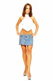 Standing woman in short jeans skirt. An friendly woman in an short jeans skirt standing in an studio Stock Photography