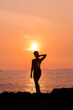 Standing woman silhouette on sea background back lit Royalty Free Stock Photos