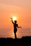 Standing woman silhouette in yoga pose on sea background back lit. Standing woman silhouette in yoga pose on sunset sea background back lit royalty free stock image