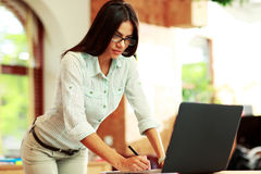 Standing woman using her laptop Royalty Free Stock Images