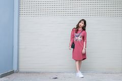 Standing Woman Wearing Red Dress Beside Roll Top Door Royalty Free Stock Images
