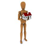 Standing wooden man holding a house with red roof Stock Photography