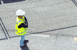 Standing worker on road works. Standing worker wearing white overalls and yellow high visibility safety jacket  on road works; horizontal orientation Stock Photography