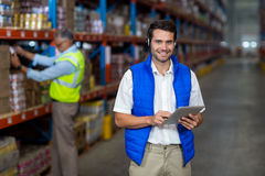 Standing worker smiling at camera while holding digital tablet Royalty Free Stock Photos