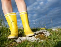 Standing in yellow boots outdoors Stock Photo