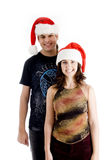 Standing young couple wearing christmas hat. Against white background Stock Photo