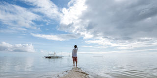 Standing young man looks at horizon on beach Stock Photos
