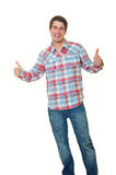 Standing young man showing thumbs up. Stylish young man standing over white background and showing thumbs up by both hands Royalty Free Stock Images