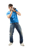 Standing young man taking photo with digital camera Stock Photos