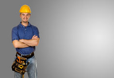 Standing young manual worker grey background stock images