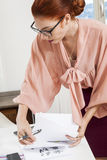 Standing Young Office Woman Writing on a Desk Stock Photo