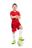 Standing young soccer player with football Stock Image