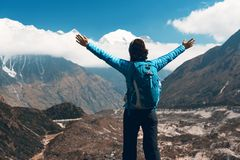 Landscape with happy girl, mountains, blue sky with clouds. Standing young woman with backpack and raised up arms on the hill and looking on mountains. Landscape Royalty Free Stock Photography