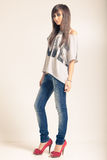 Standing young woman wearing jeans. And t-shirt with an inscription love Stock Images