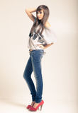 Standing young woman wearing jeans. And t-shirt with an inscription love Stock Photos