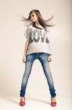 Standing young woman wearing jeans. And t-shirt with an inscription love Royalty Free Stock Images