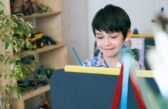 Standingnext del niño al caballete El muchacho del niño aprende la pintura por el cepillo en escuela de la clase Interior de la g Imagenes de archivo