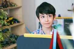 Standingnext del niño al caballete El muchacho del niño aprende la pintura por el cepillo en escuela de la clase Interior de la g Fotografía de archivo libre de regalías