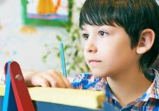 Standingnext del niño al caballete El muchacho del niño aprende la pintura por el cepillo en escuela de la clase Interior de la g Imagen de archivo