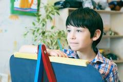 Standingnext del niño al caballete El muchacho del niño aprende la pintura por el cepillo en escuela de la clase Interior de la g Foto de archivo libre de regalías