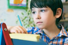 Standingnext del niño al caballete El muchacho del niño aprende la pintura por el cepillo en escuela de la clase Interior de la g Fotos de archivo libres de regalías
