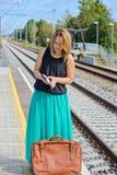 Standingon женщины станция и чтение стоковые изображения rf