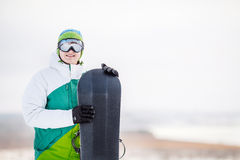 Standng del hombre joven en la nieve con la snowboard Imágenes de archivo libres de regalías