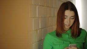 Stando accanto al muro di mattoni la giovane donna sta funzionando con il cellulare nel suo mandare un sms delle mani, archivi video