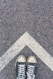 Stando sopra il segno a forma di freccia sulla strada, vista superiore Fotografia Stock