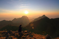 Stando sull'alta montagna nel tempo di tramonto Fotografie Stock