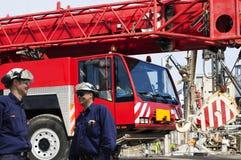 Standortarbeitskräfte und riesige mobile Kräne Stockfotos