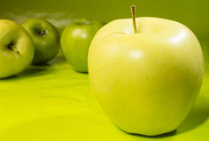 Standout. Golden apple up close other apples behind stock photography