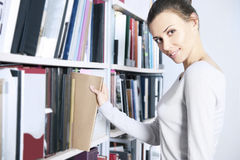 Standplätze der jungen Frauen nähern sich Bücherregal Lizenzfreie Stockfotografie