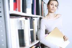 Standplätze der jungen Frauen nähern sich Bücherregal Lizenzfreie Stockfotos