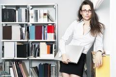 Standplätze der jungen Frauen nähern sich Bücherregal Stockfotografie