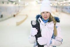 Standplatz der jungen Frau und hält Skis Stockfotografie
