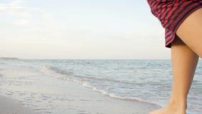 Standpunt die van jonge vrouw bij het gouden zand op zee strand stappen Vrouwelijke benen die dichtbij oceaan lopen Naakte voet d stock video