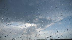 Standpunt door het windscherm van auto met regendruppels aan de bewolkte hemel Sluit omhoog van waterdruppeltjes op ruit stock video