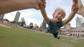 Standpunt slowmotion schot van een gelukkige vader die zijn zoon in een park spinnen stock videobeelden
