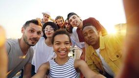 Standpunt van de Afrikaanse Amerikaanse camera van de meisjesholding en het nemen selfie met gelukkige vrienden bij partij op dak stock videobeelden