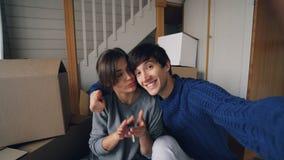 Standpunt van de knappe mens wordt geschoten die selfie met zijn mooie vrouw in het nieuwe huis kussen nemen, en sleutels koester stock video