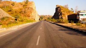 Standpunt van een hoge snelheidsauto wordt geschoten die tussen bergen en heuvels reizen die stock video