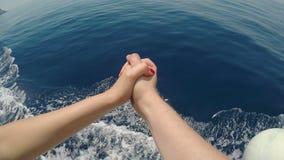Standpunt van jong paar in liefde joying handen terwijl reis op een cruiseschip over het overzees - stock footage