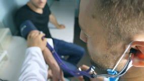Standpunt van mannelijke arts die bloeddruk controleren aan de jonge mens Impulsmeting aan patiënt stock footage