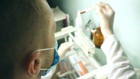 Standpunt van mannelijke arts met beschermende handschoenen die test-buis met bloed houden en steekproeven op het ziekenhuis test stock video