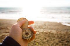 Standpuntfoto van het kompas van de mensenholding in de hand op de overzeese en strandachtergrond Royalty-vrije Stock Afbeeldingen