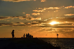 She stands alone at sunset. This is a photo of a lady (and crowd) watching the sunset from a Gulf of Mexico jetty Royalty Free Stock Photos