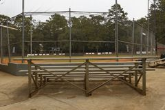 The Stands and the Baseball Field. Aluminum stands before a chain-link fence that surrounds a local baseball field Stock Photo